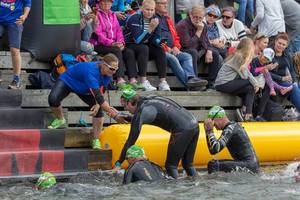 Woman of the Ironman team helps swimmer to climb out of the lake after the first triathlon stage
