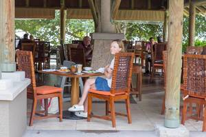 Woman on vacation with cappuccino on wooden rattan chair in cafe of Constance Ephelia Resort in Mahé, Seychelles Island