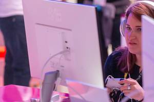 Woman plays with a Google Stadia controller in front of a white monitor at Gamescom trade fair in Cologne, Germany