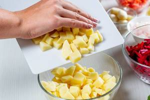 Woman pours sliced potatoes in a glass bowl