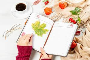 Woman puts maple leaf in empty notebook on autumn background of white table with scarf, coffee Cup and glasses (Flip 2019)