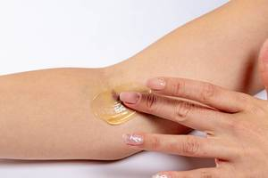 Woman putting medical gel on the bruise after intravenous blood sampling (Flip 2019)