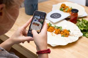 Woman takes a food picture with her smartphone