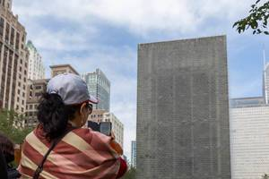 Woman takes a photo with her smartphone at the Crown Fountain at Millennium Park in Chicago