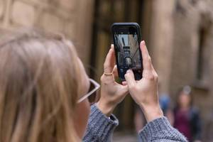 "Woman taking a phone picture of the tourist attraction and mediterranean Skywalk ""Pont Gòtic"" in the Carrer del Bisbe Alley in Barcelona, Spain"