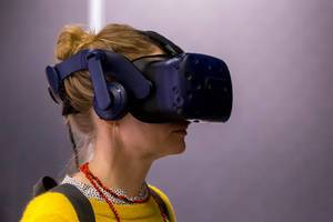 Woman with yellow sweater testing the HTC Vive VR glasses on the Photokina in Cologne