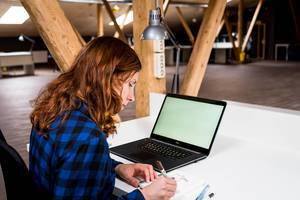 Woman works in an open space at a desk with a notebook