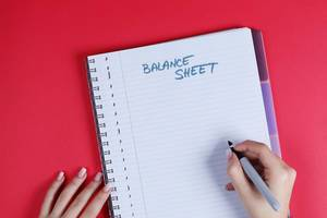 Woman writing Balance Sheet text on notebook, red background