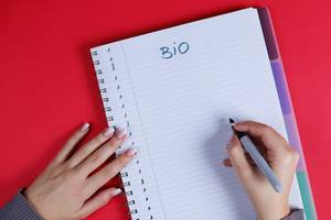 Woman writing Bio text on notebook, red background