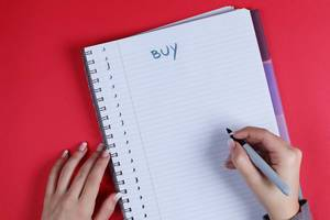 Woman writing Buy text on notebook, red background