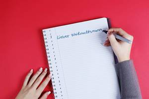 Woman writing Lieber Weihnachtsmann text on notebook, red background