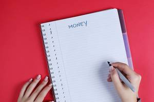 Woman writing Money text on notebook, red background