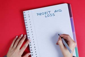 Woman writing Profit and Loss text on notebook, red background
