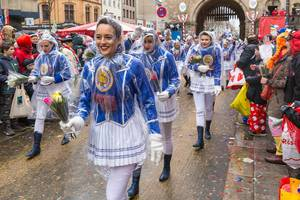 Women parade in traditional blue-white costumes and rain ponchos and hold roses in their hands as the Rose Monday parade starts at Severinsburgtor in Cologne