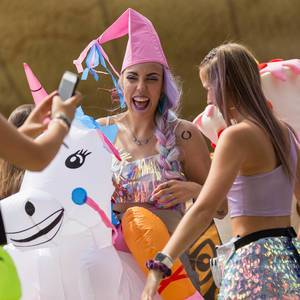 Women with colorful hair laugh and ride on inflatable unicorns at the Tomorrowland Festival