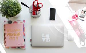 Womens desk at home with a bottle , macbook, notebooks and an iphone