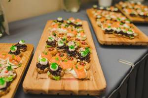 Wood Plates Of Salmon, Pork and Cream Canapes (Flip 2019)