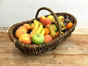 Wooden basket with fresh different fruits on a wooden table