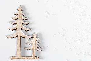 Wooden figures of a large and small Christmas tree on a white background with snow. Top view (Flip 2019)