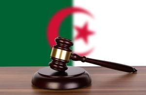 Wooden gavel and flag of Algeria