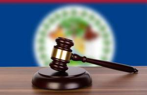 Wooden gavel and flag of Belize