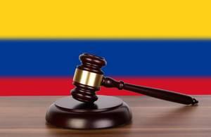 Wooden gavel and flag of Colombia