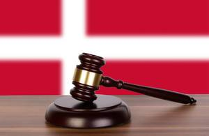 Wooden gavel and flag of Denmark