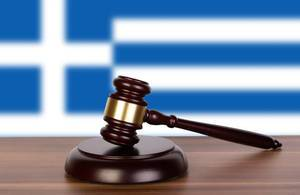Wooden gavel and flag of Greece