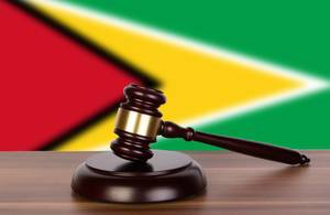 Wooden gavel and flag of Guyana