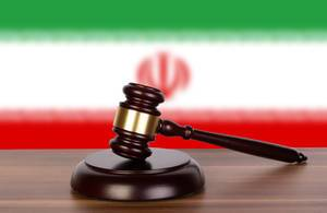 Wooden gavel and flag of Iran