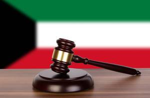 Wooden gavel and flag of Kuwait