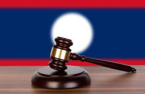Wooden gavel and flag of Laos