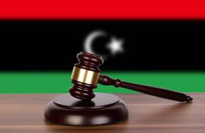 Wooden gavel and flag of Libya
