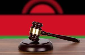 Wooden gavel and flag of Malawi
