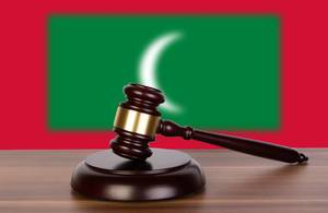 Wooden gavel and flag of Maldives