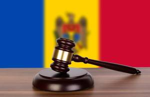 Wooden gavel and flag of Moldova