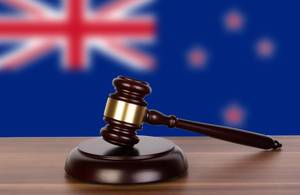 Wooden gavel and flag of New Zealand