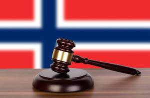 Wooden gavel and flag of Norway