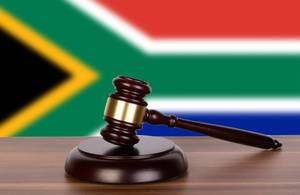 Wooden gavel and flag of South Africa