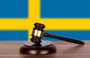 Wooden gavel and flag of Sweden