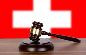 Wooden gavel and flag of Switzerland