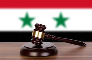 Wooden gavel and flag of Syria