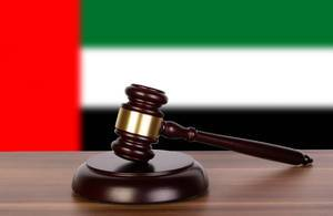 Wooden gavel and flag of United Arab Emirates