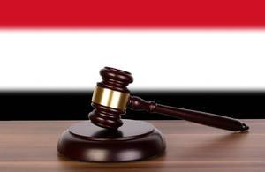 Wooden gavel and flag of Yemen