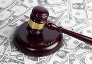 Wooden judge gavel on hundred dollar banknotes