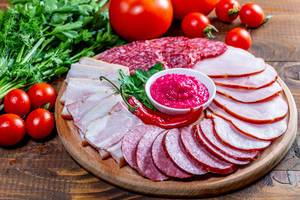 Wooden kitchen Board with sliced smoked sausages, salami, ham and meat with sauce on wooden table (Flip 2019)
