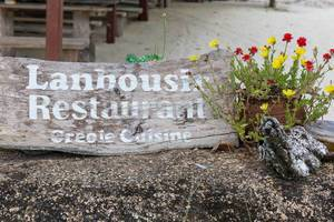 Wooden sign of Lanbousir Restaurant - Creole Cuisine in La Digue in the Seychelles