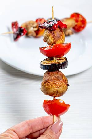 Wooden skewer with mushrooms, tomatoes, eggplant and sweet pepper in hand
