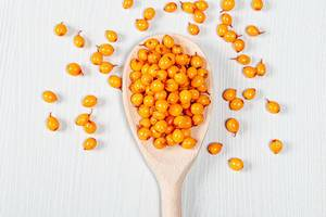 Wooden spoon with ripe fresh sea buckthorn berries. The view from the top (Flip 2019)