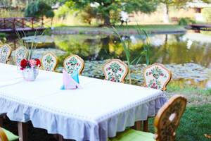 Wooden table and chairs ready for party, by the lake